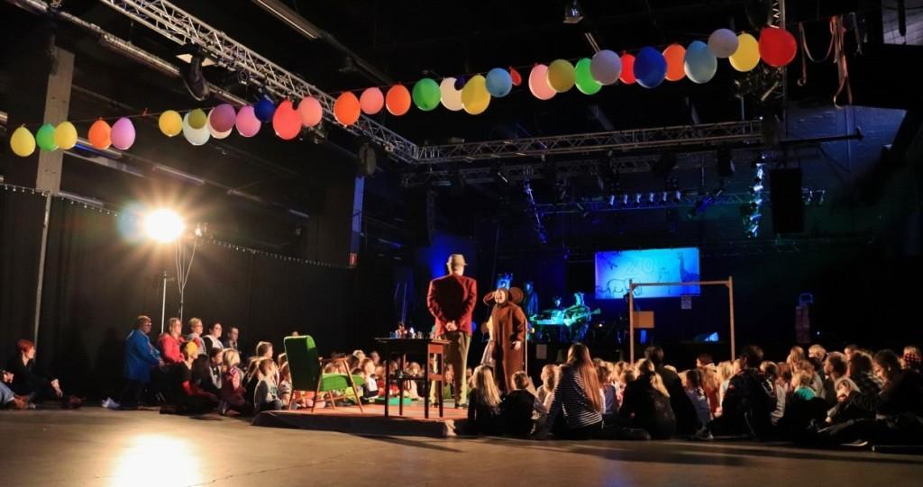 Kuvassa ilmapalloviiri, jossa eriväirisiä ilmapalloja. Teatteriesitys jossa ihmiset istuvat lattialla.