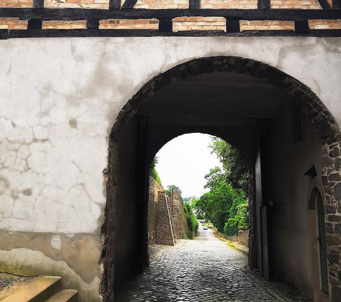 Muuriportin holvikäytävän läpi näkymä vanhalle kivikadulle.