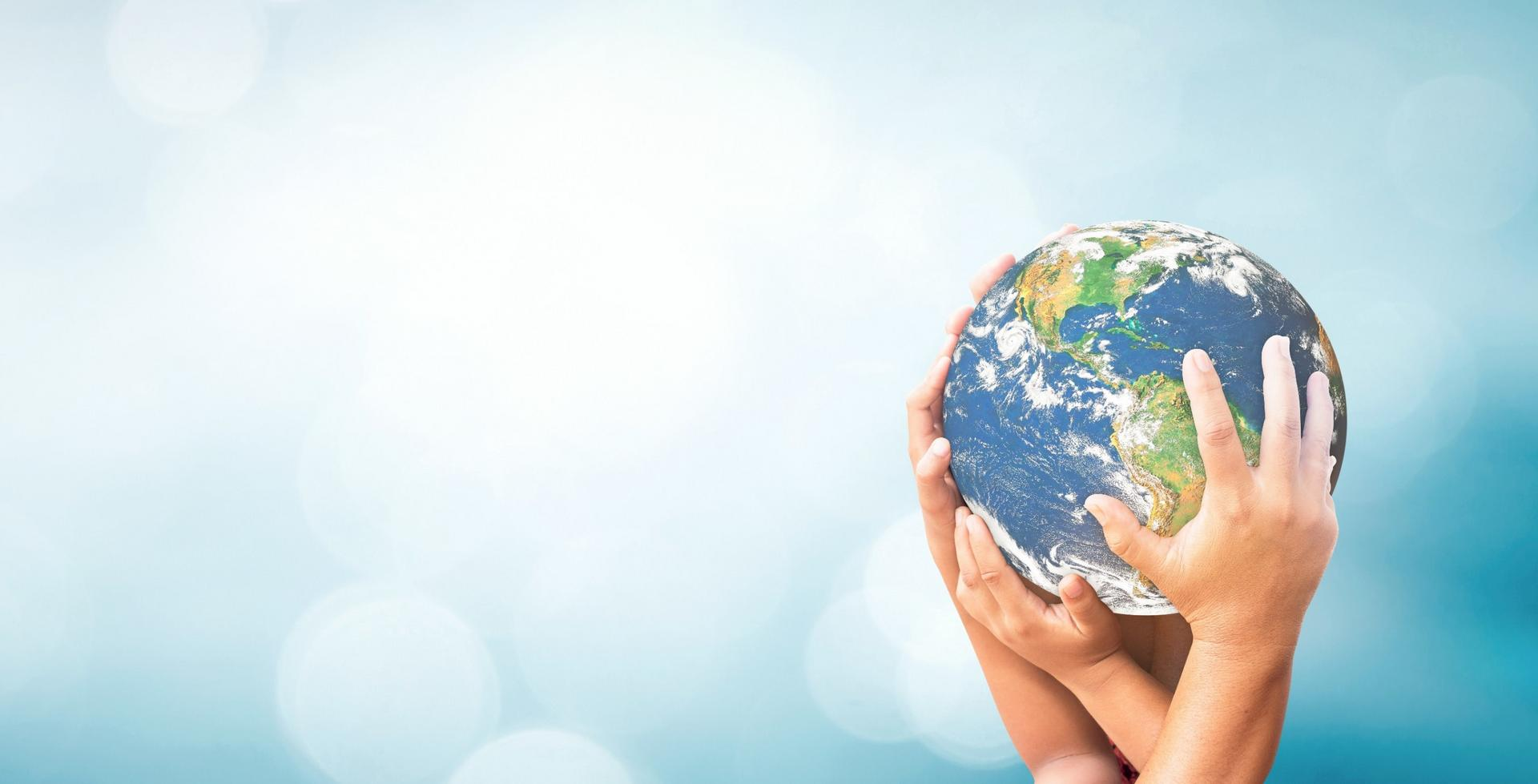 Hands holding globe on light blue background