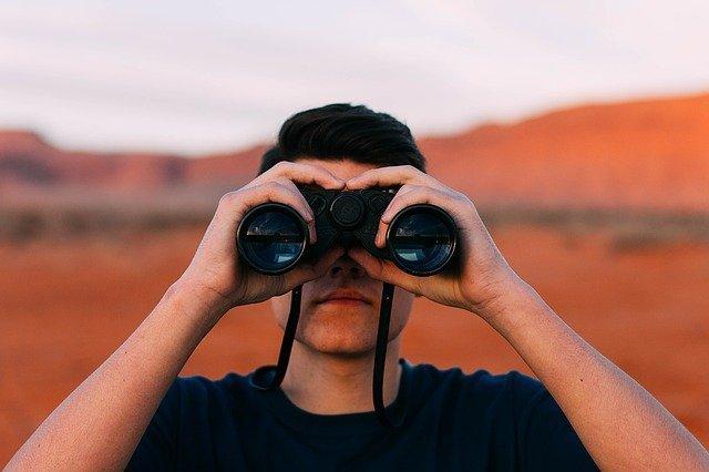 Mies katsoo kiikarilla kaukaisuuteen