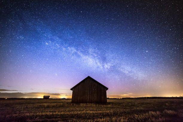 Öinen peltomaisema Etelä-Pohjanmaalta, jossa on lato tähtitaivasta vasten.