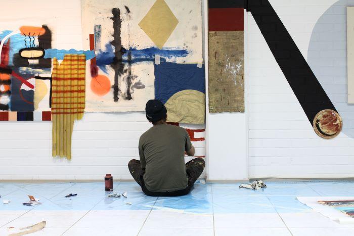 Taiteilija istuu ja maalaa värikästä taideteosta seinään.