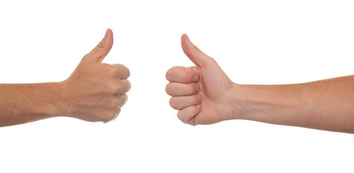 Two hands opposite to each other with thumbs up on white background