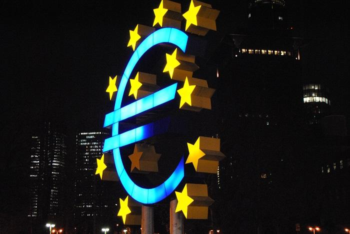 Euro sign on blue surrounded by yellow stars with a city skyline at night