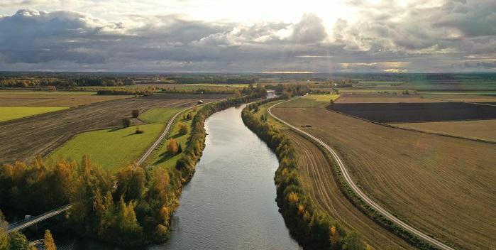 Ilmakuva lakeusmaisemasta, jossa peltojen keskellä virtaa joki