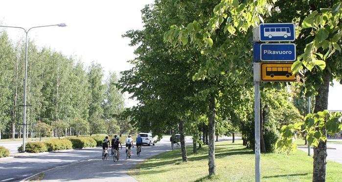 Kaupunkimaisema, jossa autoja, pyöräilijöitä ja bussipysäkkikyltti