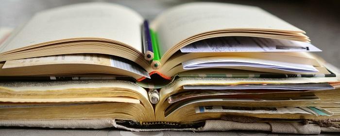 Avoinna olevia kirjoja ja puuvärikyniä pinossa