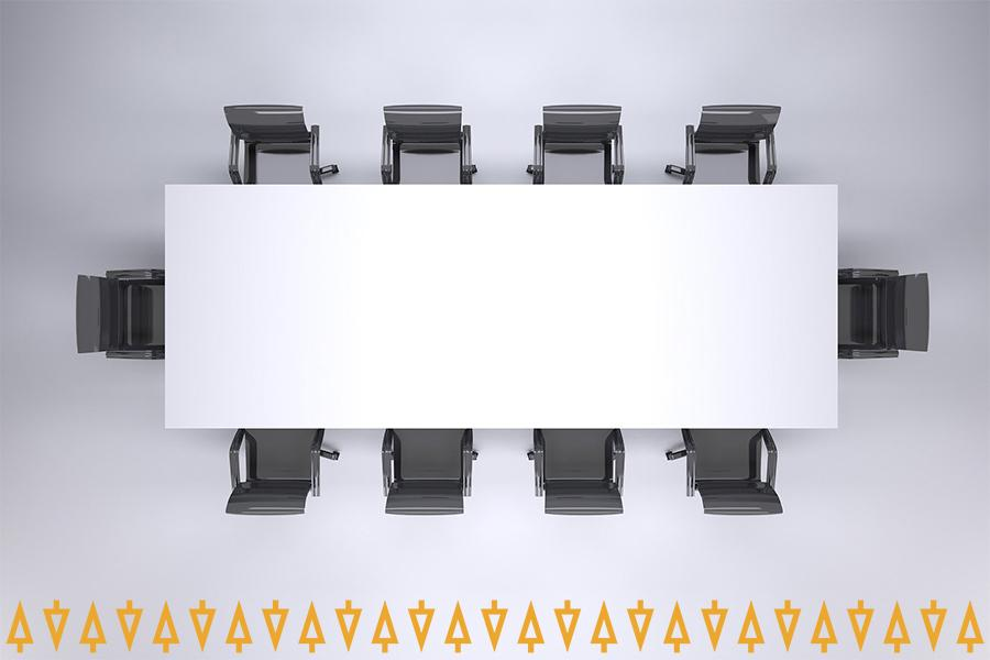 Kokoustilan pöytä, jonka ympärillä on kymmenen tyhjää tuolia.