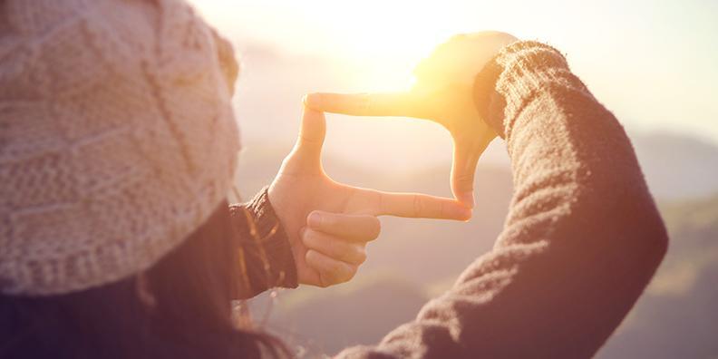Nainen katsoo sormien lomasta aurinkoon.