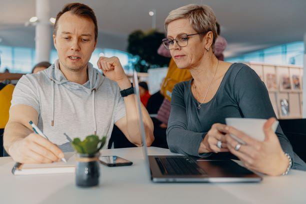 Mies ja nainen työskentelevät kannettavan tietokoneen ääressä.