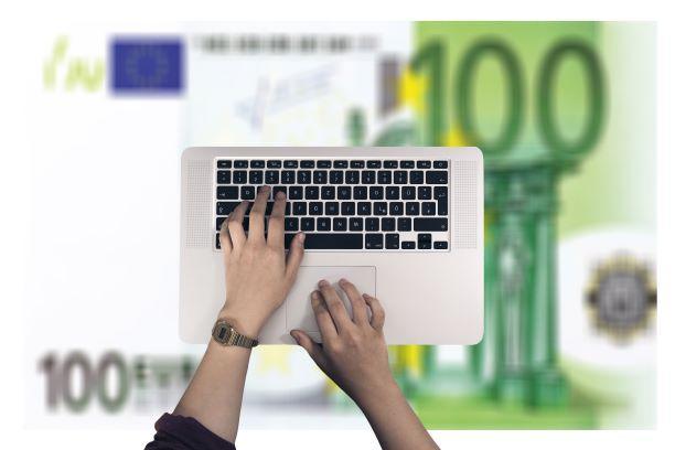 100 euron seteli, jonka päällä kannettava tietokone ja kädet.