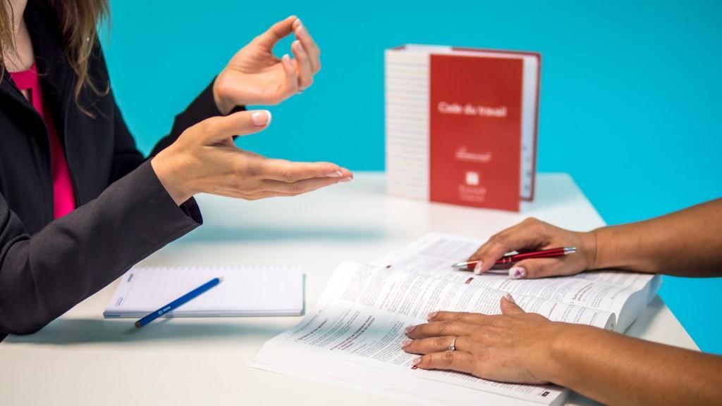 Pöydän ympärillä näkyy kahden ihmisen kädet. Neuvontatilanne.
