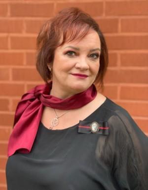 Kuvassa Anu Katajamäki punaisen tiiliseinän edustalla