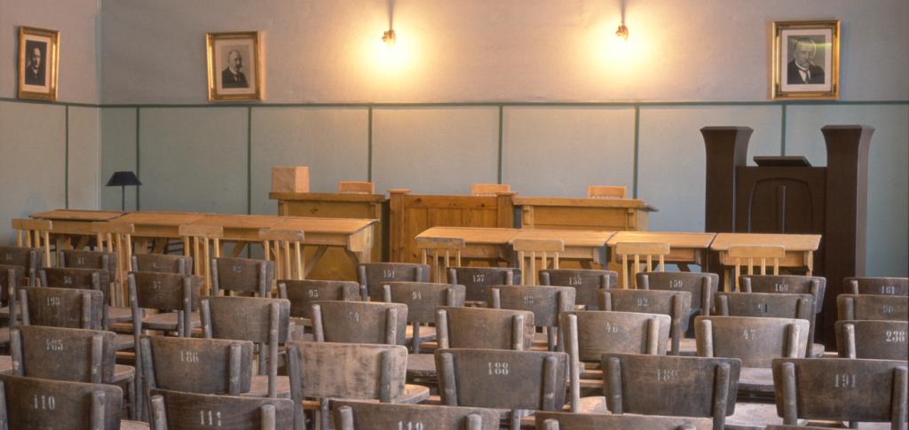 Kauhajoen eduskuntamuseon sisätilat, joissa vanhoja puisia numeroituja tuoleja sekä pulpetteja. Seinillä Suomen presidenttien valokuvia.