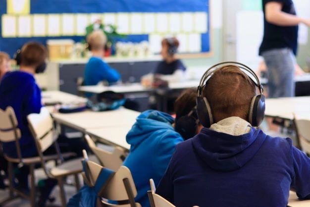 Lapset kuuntelevat musiikkia tablet-tietokoneelta kuulokkeet päässä.
